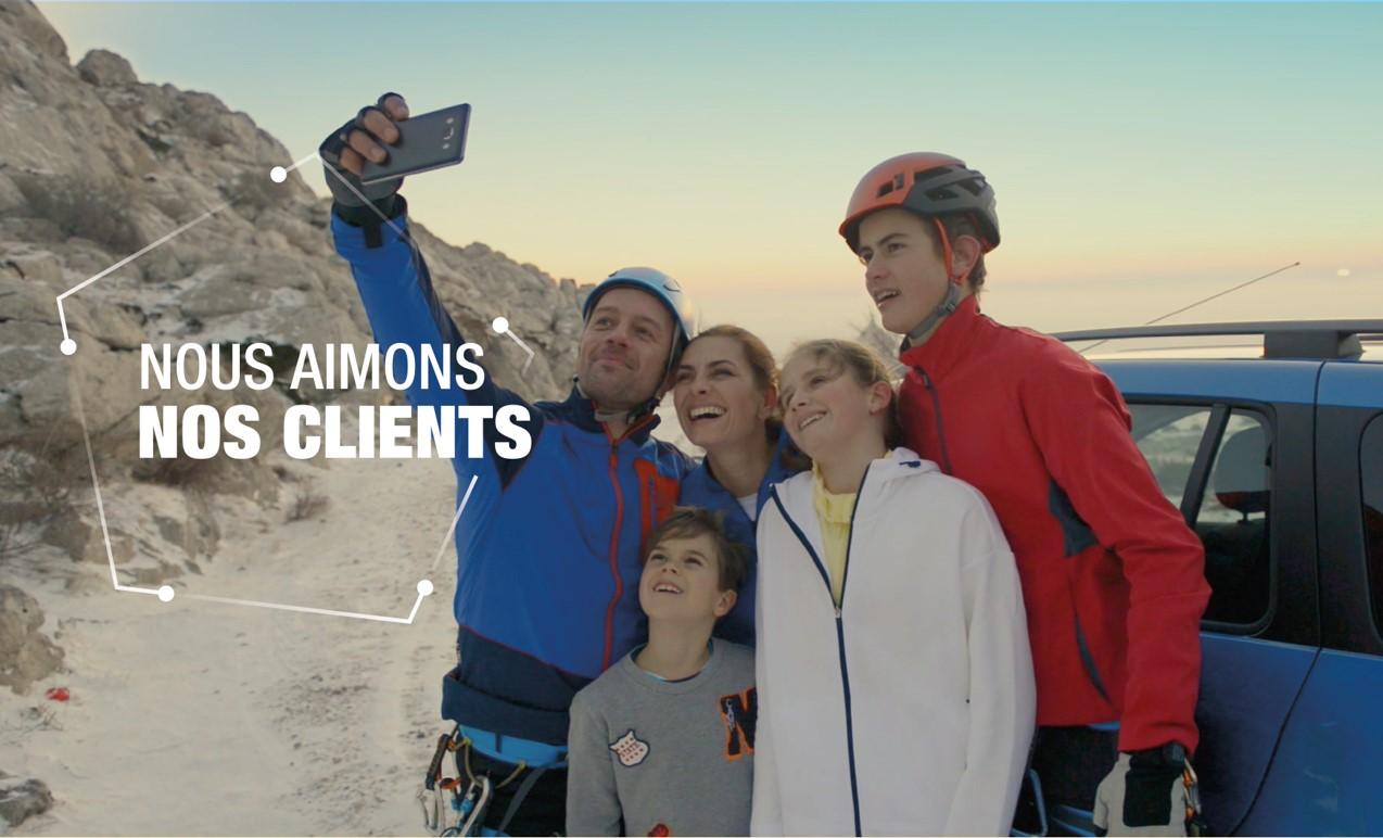 """Illustration de notre première valeur """"Nous aimons nos clients"""", représentant une famille en voyage, rassemblée autour d'un véhicule de notre marque"""